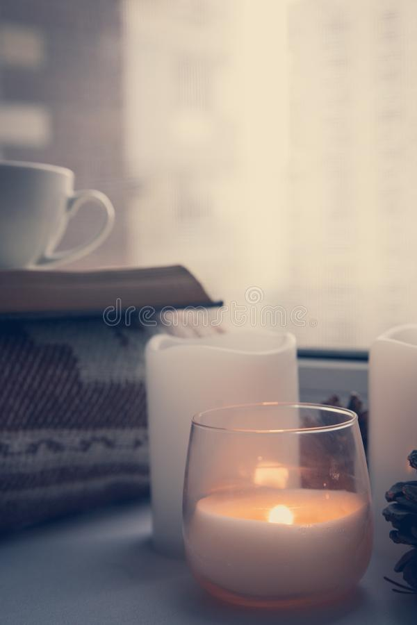 Details of still life in the home interior. Sweater, cup, wool, cozy, book, candle. Moody. Cosy autumn winter concept. stock images