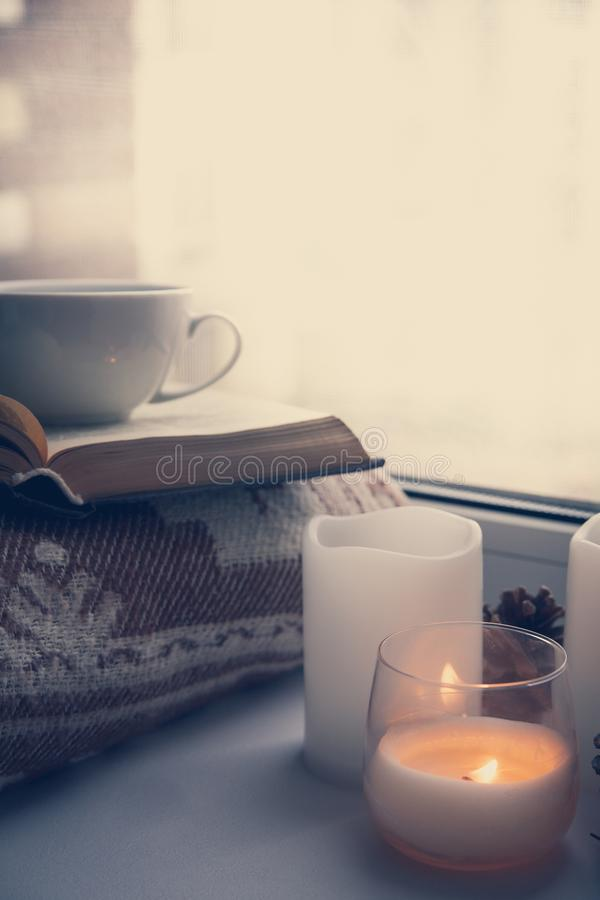 Details of still life in the home interior. Sweater, cup, wool, cozy, book, candle. Moody. Cosy autumn winter concept. royalty free stock photos