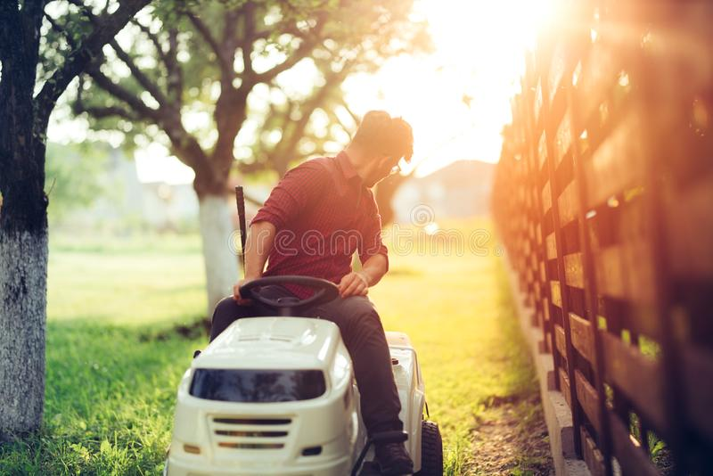 Details during sunset hour. Man working on ride-on lawn mower. Gardening details during sunset hour. Man working on ride-on lawn mower stock photography