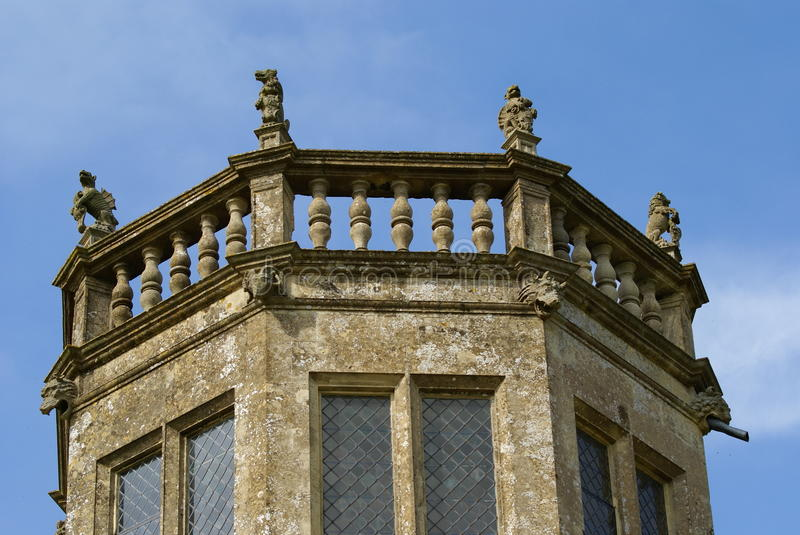 Details of the tower of Lacock Abbey in England, Europe. Tower with griffin statues of Lacock Abbey in the village of Lacock, Wiltshire, England, was founded in royalty free stock photography