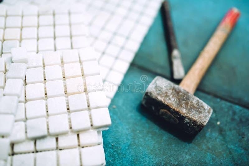 Details van bouwhulpmiddelen, badkamers en keukenvernieuwing - stukken van mozaïekkeramische tegels en rubberhamer royalty-vrije stock foto