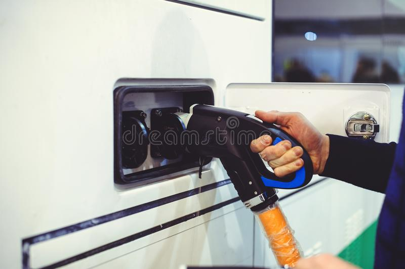 Details van elektrisch voertuig het laden het vervoer van de stadsbus Groen en hernieuwbare energiebronnen de mens houdt in zijn  stock foto