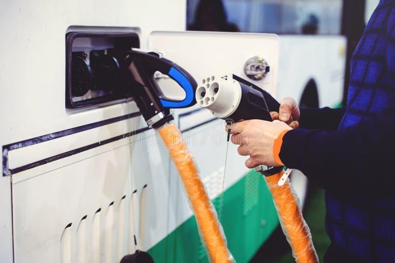 Details van elektrisch voertuig het laden het vervoer van de stadsbus Groen en hernieuwbare energiebronnen de mens houdt in zijn  stock foto's
