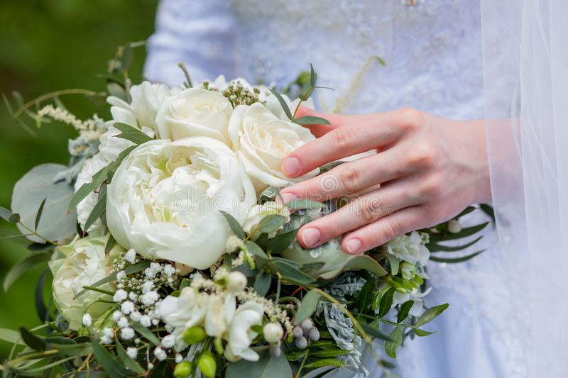 Details of the wedding morning. Wedding bouquet in the hands of the bride in soft pastel colors stock photography