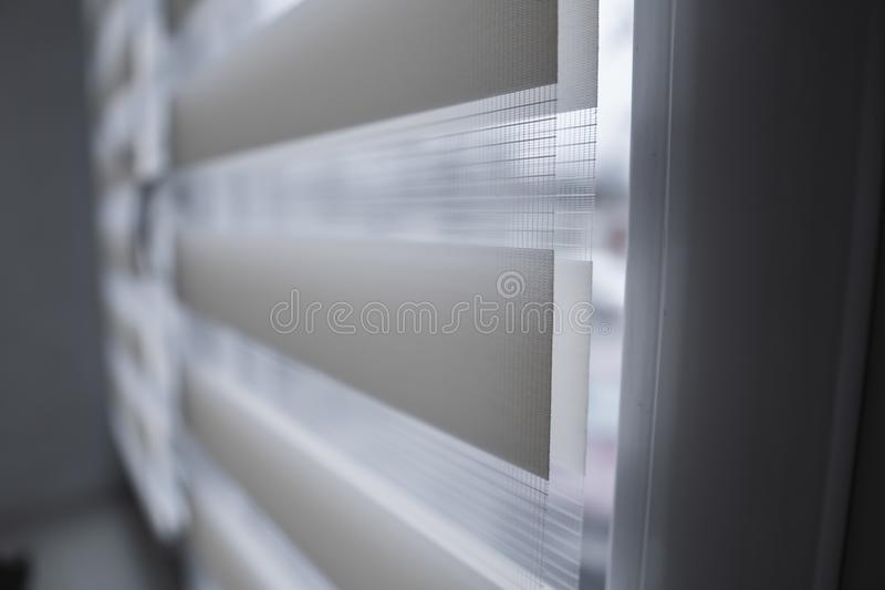Details of white fabric roller blinds on the white plastic window in the living room. Close up on roll curtains indoor. Details of white fabric roller blinds on royalty free stock photos