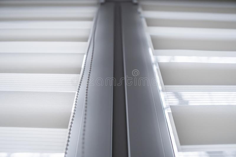 Details of white fabric roller blinds on the white plastic window in the living room. Close up on roll curtains indoor. Details of white fabric roller blinds on royalty free stock photo