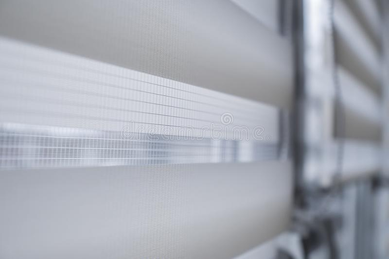 Details of white fabric roller blinds on the white plastic window in the living room. Close up on roll curtains indoor. Details of white fabric roller blinds on royalty free stock image