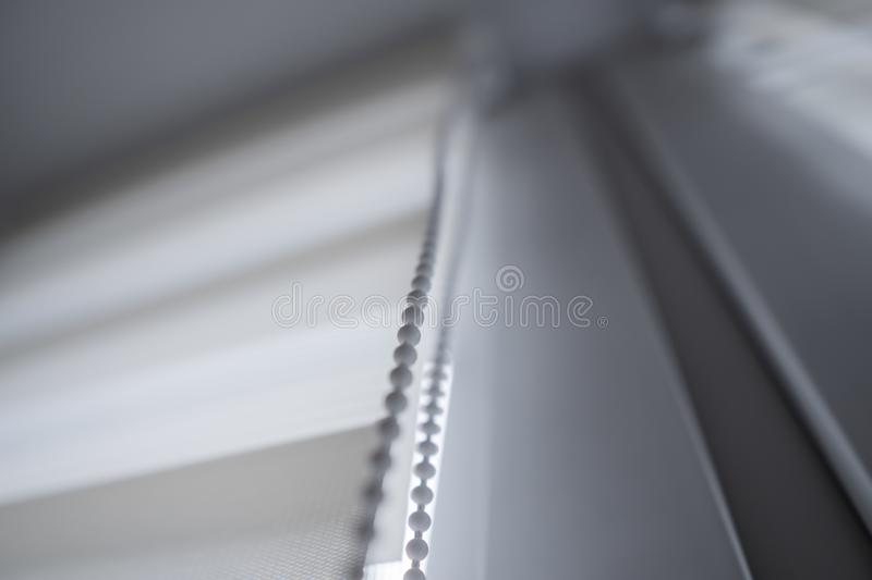 Details of white fabric roller blinds on the white plastic window in the living room. Close up on roll curtains indoor. Details of white fabric roller blinds on stock photo