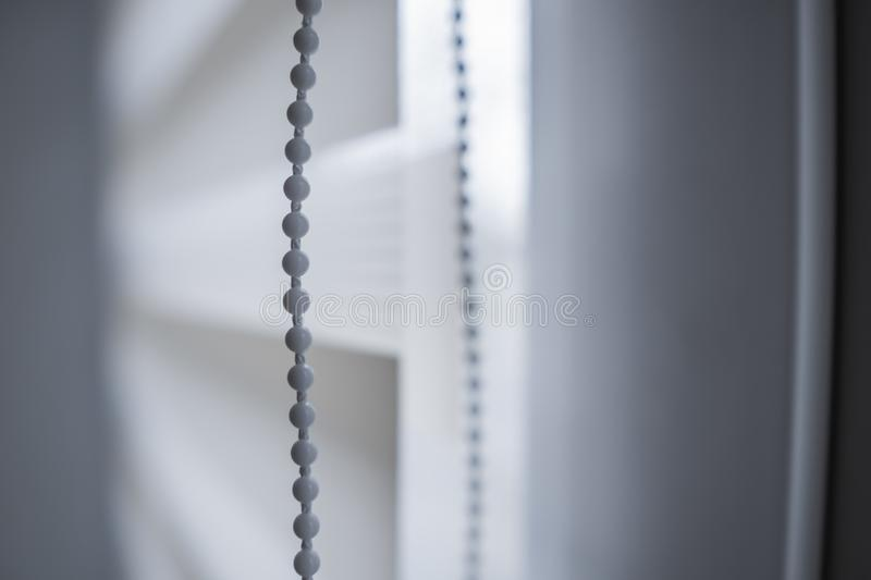 Details of white fabric roller blinds on the white plastic window in the living room. Close up on roll curtains indoor. Details of white fabric roller blinds on stock photography
