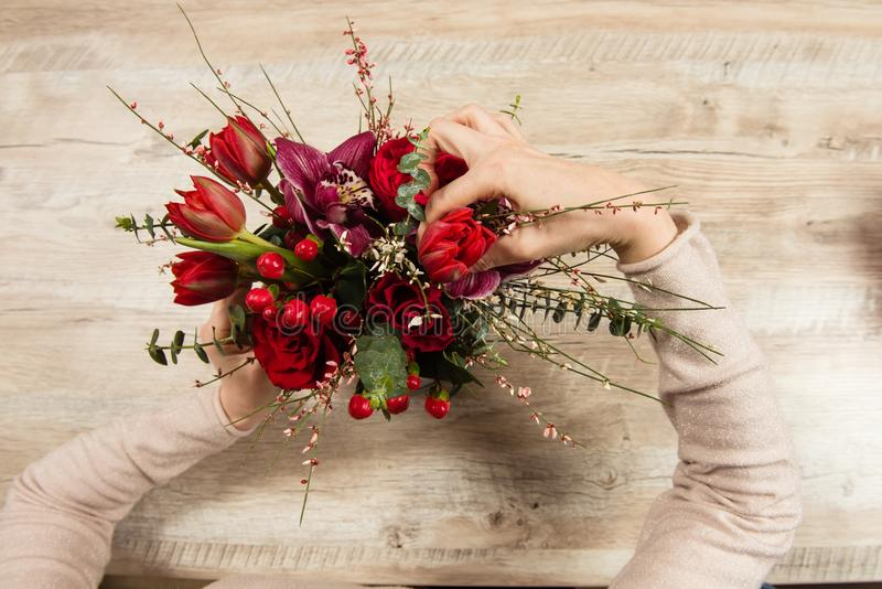 Female hands arrange red bouquet stock photography