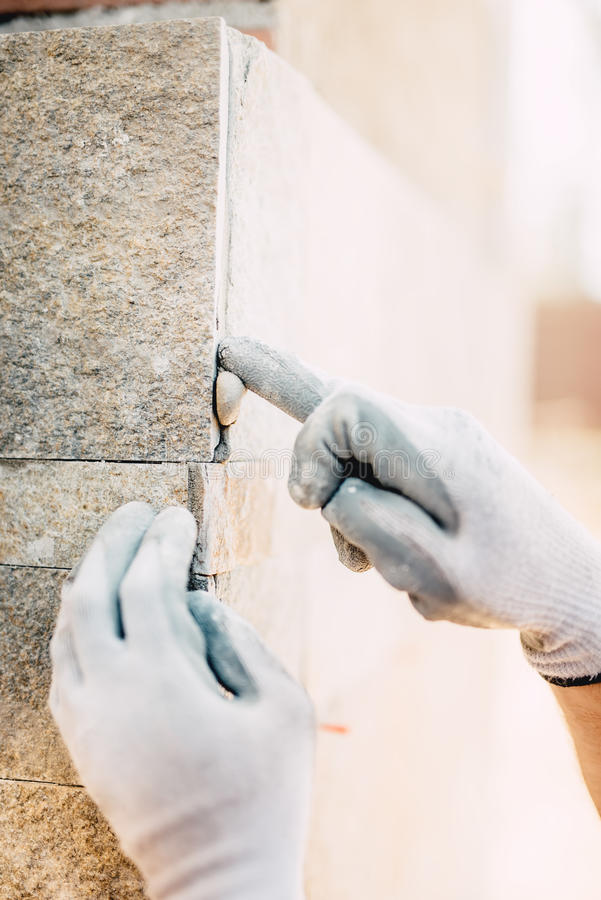 details of worker hands plastering and installing stone on construction site. perfection details in construction industry royalty free stock images