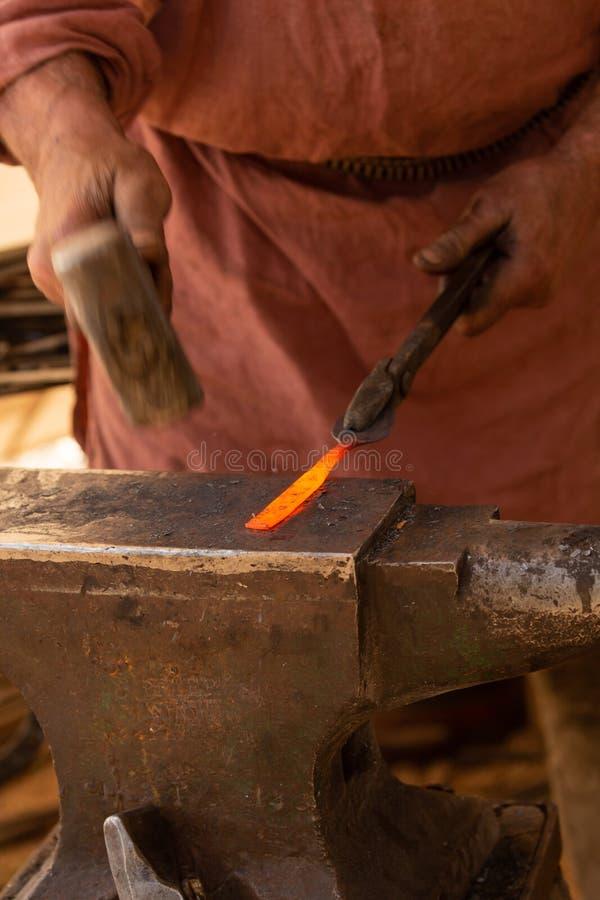 Detailschot van de handen van een smid aangezien hij op het roodgloeiende uiteinde van een metaalbar hamert stock afbeeldingen