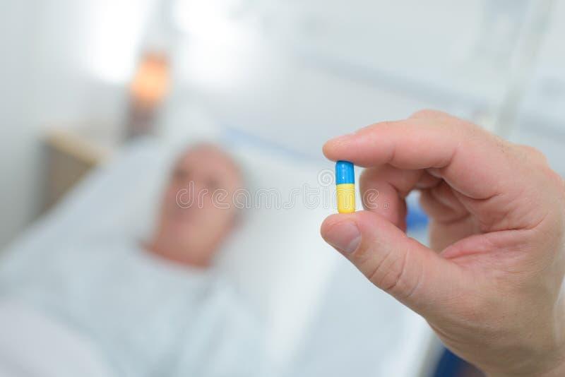 Detailverpleegster die pillen geven aan patiënt stock afbeeldingen