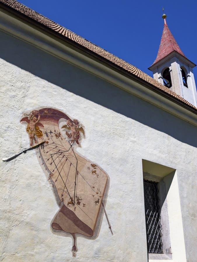 Detalhe arquitetónico exterior com um relógio de sol da igreja da peregrinação de St John de Nepomuk, em Lana di Sopra ou em Ober imagem de stock royalty free