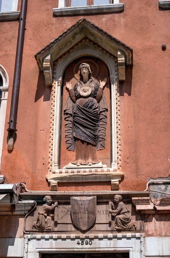 Detalhe arquitetónico, um bas-relevo de pedra da Virgem Maria e Jesus pequeno na parede de uma casa em Veneza retrato fotos de stock royalty free