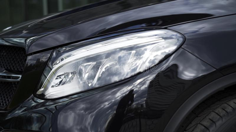Detalhe ascendente próximo para um dos faróis do diodo emissor de luz de um carro preto moderno estoque Detalhe exterior, farol d foto de stock