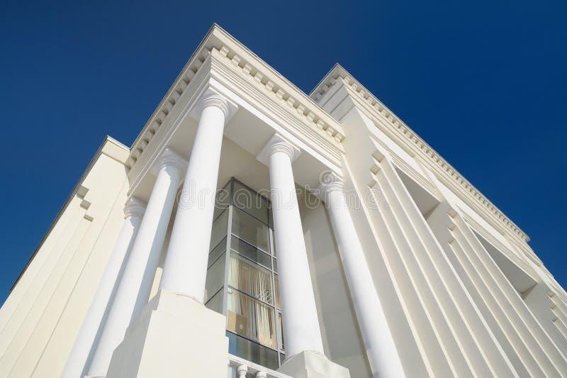 Detalhe branco da fachada da construção do estilo clássico com as colunas contra imagem de stock