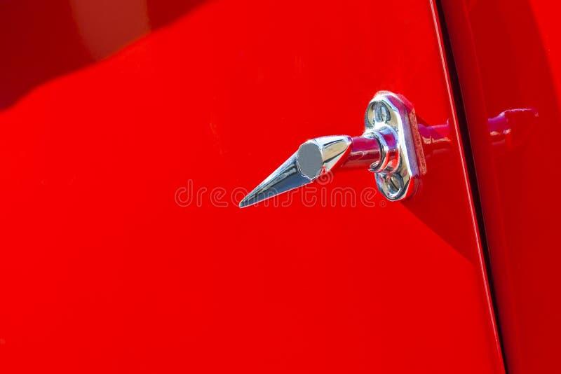 Detalhe cromado do punho no fundo vermelho de um carro de esportes do vintage imagens de stock royalty free