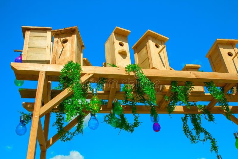 Detalhe da decoração no jardim um arco de madeira com casas de pássaros e um jardim de lâmpadas foto de stock