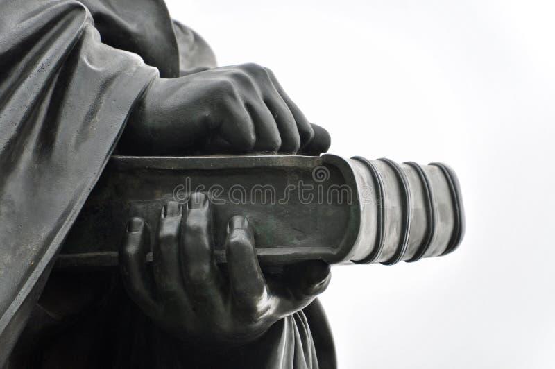 Detalhe da estátua de bronze: duas mãos que guardam o livro fotos de stock