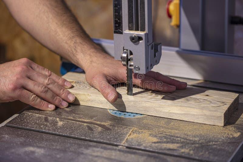 Detalhe da mão de um carpinteiro ao lado de uma lâmina de serra da faixa fotos de stock