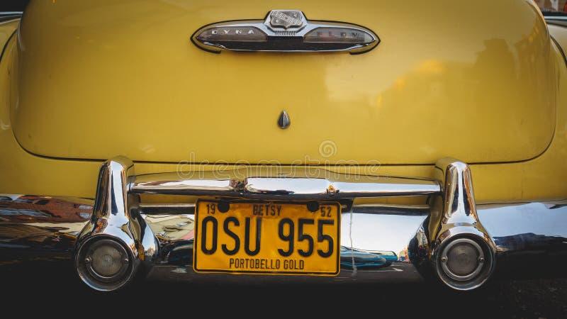 Detalhe da parte traseira de um carro amarelo do vintage na estrada de Portobello Londres Reino Unido, em julho de 2017 foto de stock royalty free