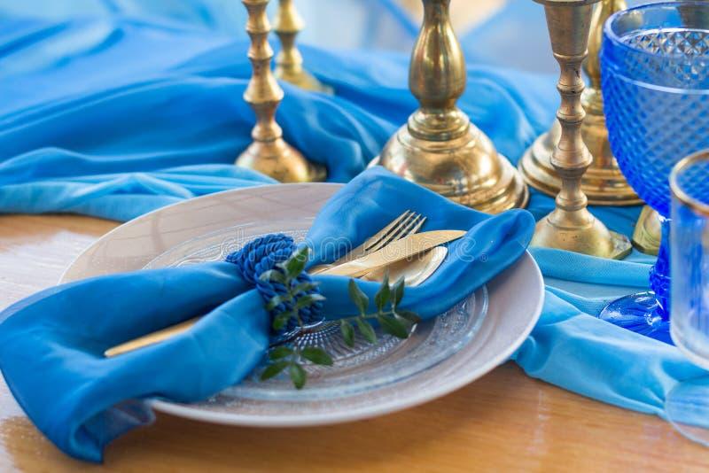 Detalhe da tabela de jantar do casamento no branco, no ouro e na cor azul selec imagens de stock royalty free