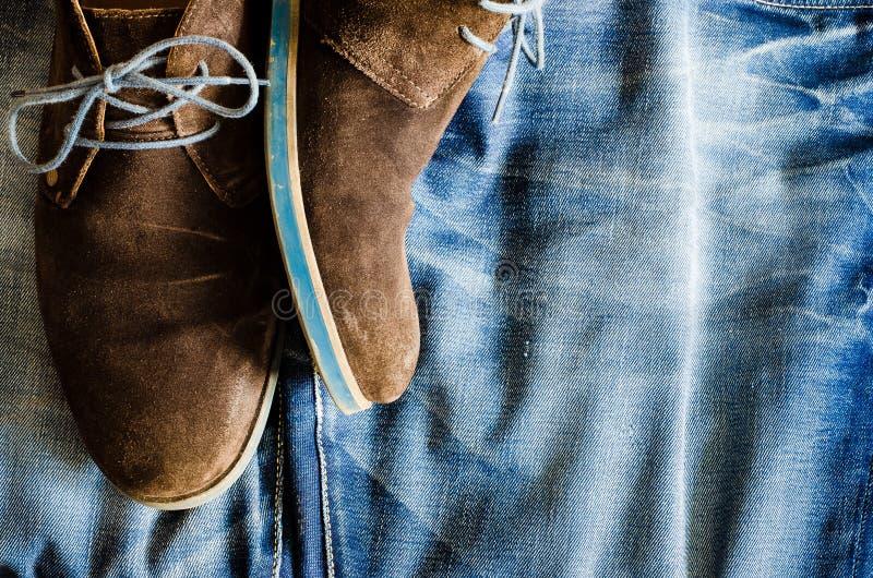 Detalhe das sapatas de couro do vintage na tela da sarja de Nimes foto de stock