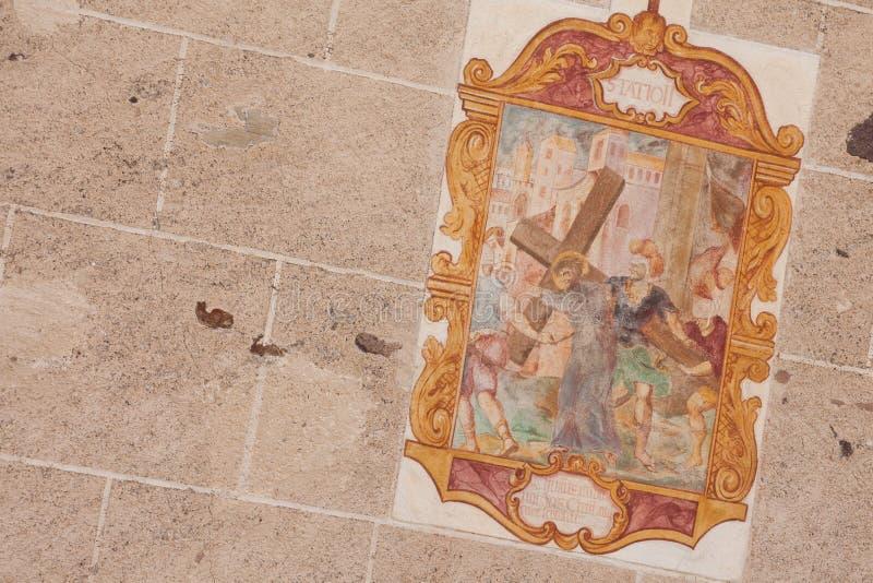 Detalhe de alguma pintura fora da igreja pequena de StMagdalena em Val di Funes que representa um momento na maneira da cruz foto de stock