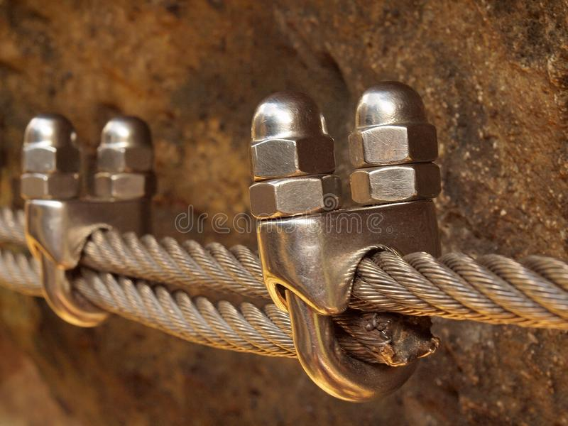 Detalhe de braçadeira do parafuso na extremidade da corda do irone Os montanhistas passam a corda torcida fixada no bloco pelos g imagem de stock