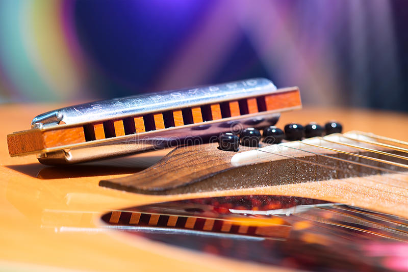Detalhe de cordas da guitarra com a harmônica apoiada para o país MU fotografia de stock