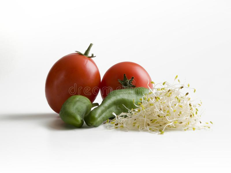 Detalhe de dois tomates vermelhos, de pimentas verdes e de broto de soja fotografia de stock