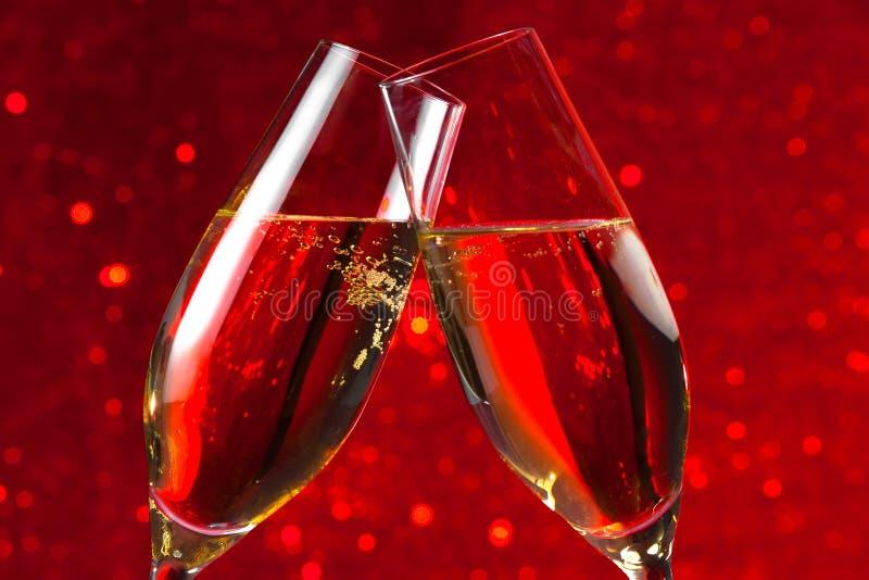 Detalhe de duas flautas de champanhe no fundo do bokeh da luz vermelha fotos de stock