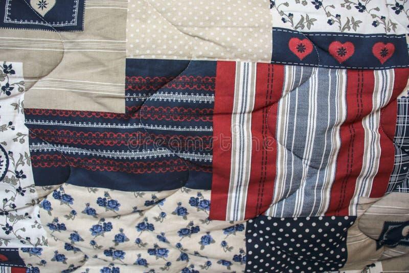 Detalhe de edredão de retalhos azul e vermelha com acolchoado da mão fotografia de stock royalty free