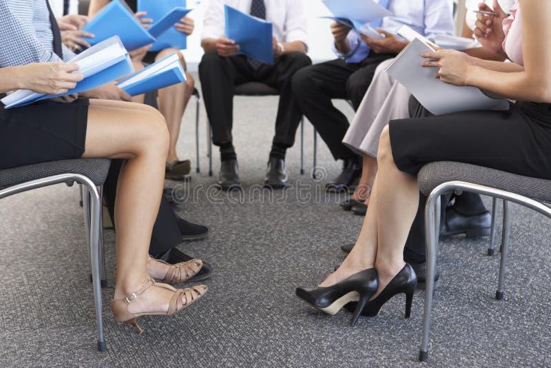 Detalhe de empresários assentados no círculo no seminário da empresa imagem de stock