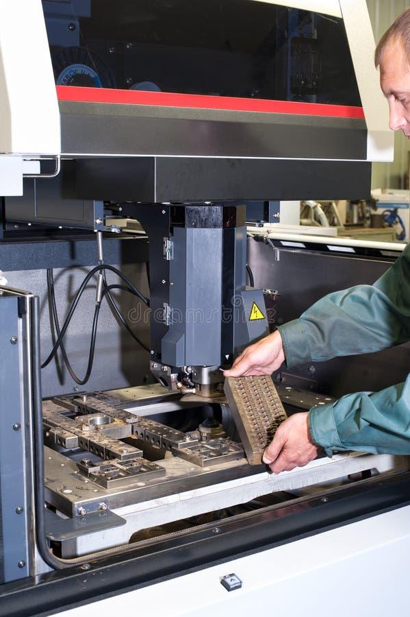Detalhe de exame do metal do trabalhador na máquina industrial do cnc imagem de stock