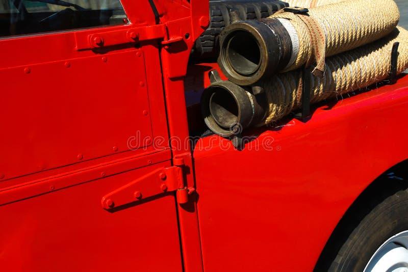 Detalhe de firetruck vermelho do vintage com mangueira de fogo imagem de stock