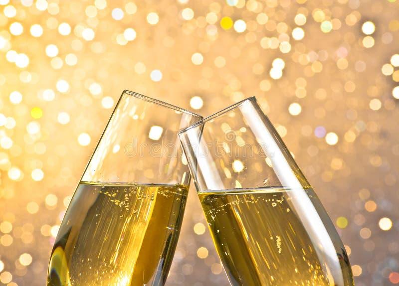 Detalhe de flautas de champanhe com bolhas douradas no fundo claro do bokeh fotos de stock