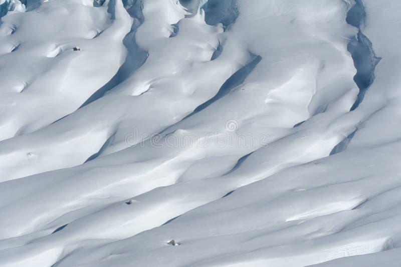 Detalhe de fluxo e de fissuras da geleira cobertos pela neve no inverno fotografia de stock