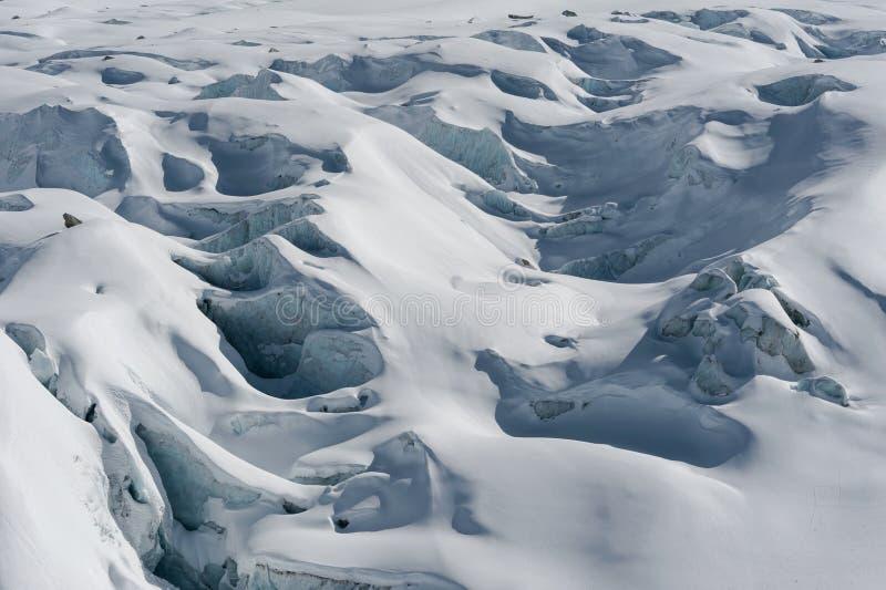 Detalhe de fluxo e de fissuras da geleira cobertos pela neve no inverno foto de stock