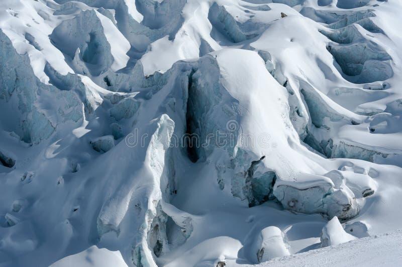 Detalhe de fluxo e de fissuras da geleira cobertos pela neve no inverno imagem de stock