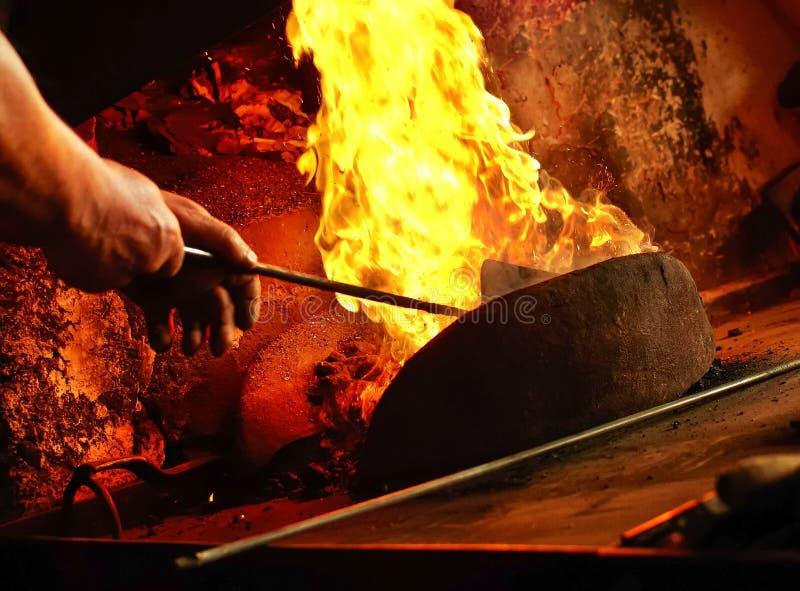 Detalhe de forja do ferreiro s com chamas fortes Equipa as mãos que estabelecem o fogo na forja imagem de stock royalty free