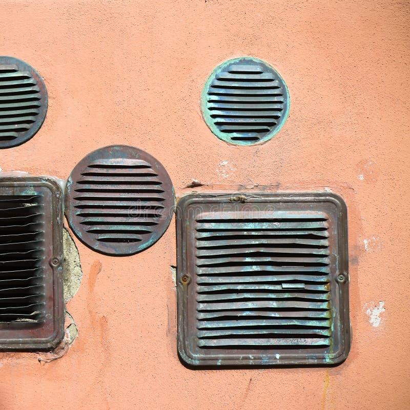 Detalhe de grades de cobre velhas de uma ventilação em uma parede emplastrada colorida imagem de stock royalty free