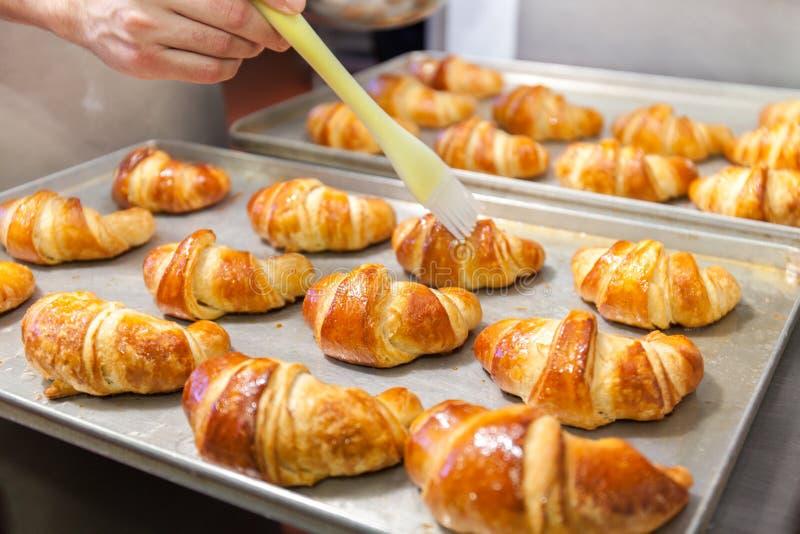 Detalhe de mãos que preparam o croissant francês na cor foto de stock royalty free
