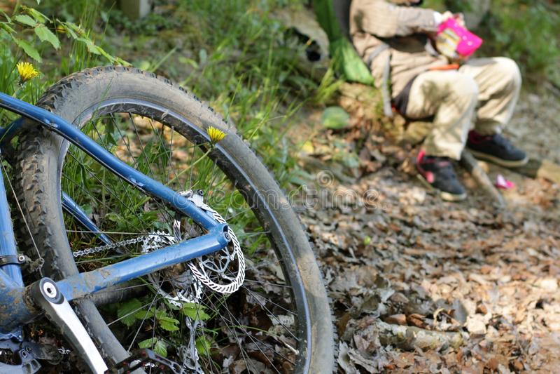 Detalhe de Mountain bike azul na floresta com criança de descanso imagens de stock