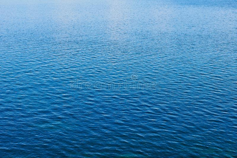 Detalhe de ondinhas múltiplas na água do mar azul calma imagem de stock royalty free