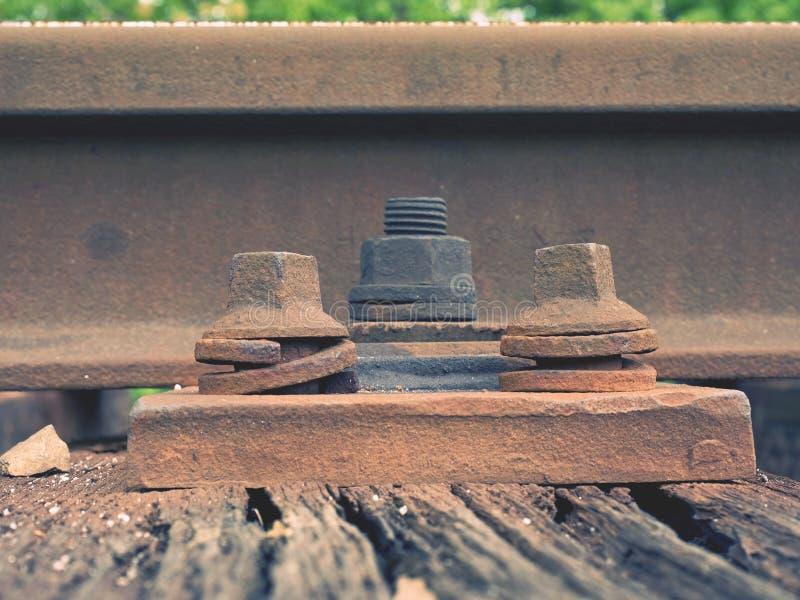 Detalhe de parafusos e de porca oxidados na trilha de estrada de ferro velha Laço de madeira de Rooten com porcas oxidadas - e -  foto de stock