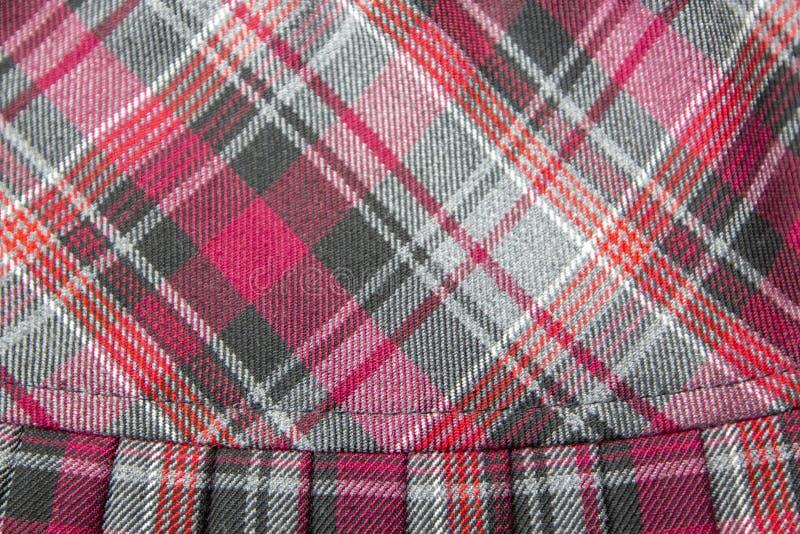 Detalhe de saia plissada da forma manta nova: algodão vermelho, marrom, cinzento da tela da farda da escola da tartã/material de  imagens de stock royalty free