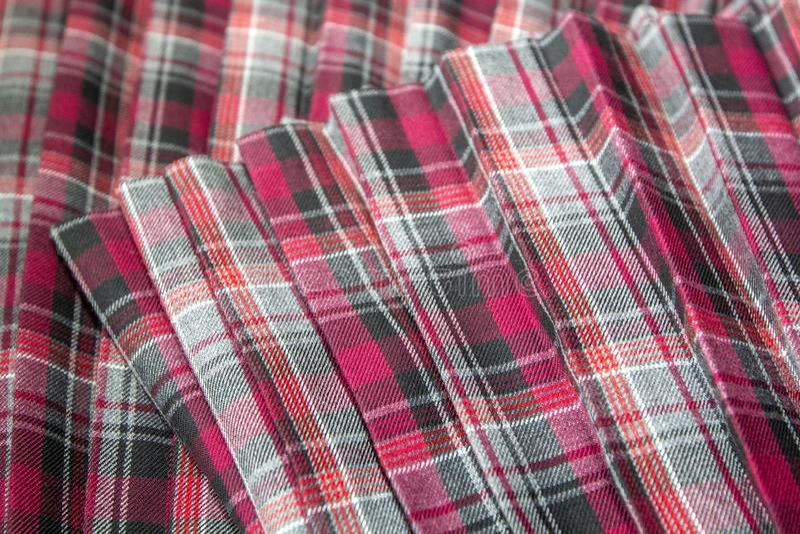 Detalhe de saia plissada da forma manta nova: algodão vermelho, marrom, cinzento da tela da farda da escola da tartã/material de  imagens de stock