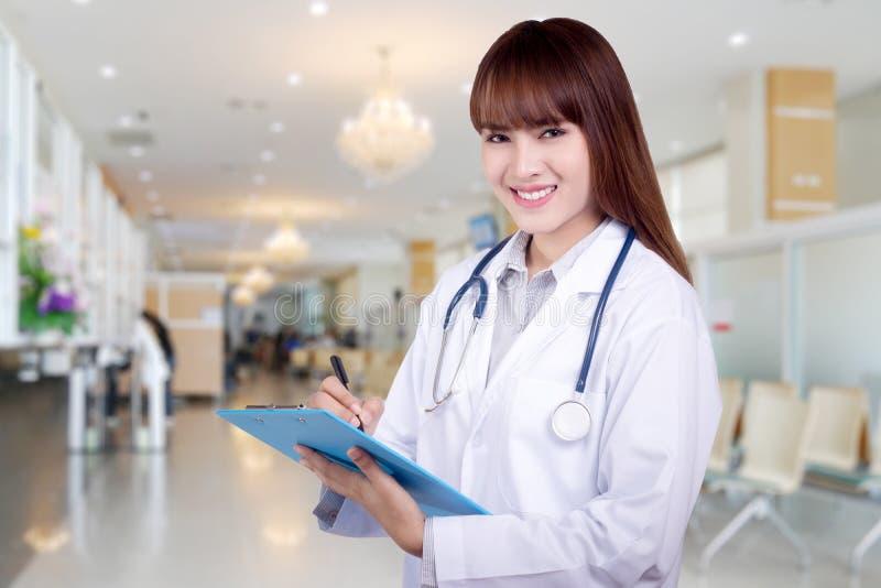 Detalhe de um doutor asiático novo da mulher que guarda uma posição da prancheta no fundo do hospital Conceito dos cuidados m?dic fotos de stock